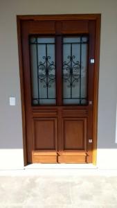 Porta externa pivotante com almofada inferior e vidro/grade superior