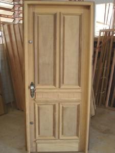 Porta externa com almofadas e aplique central