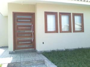Porta externa pivotante com detalhes para vidros
