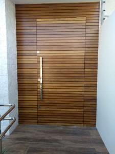 Porta externa pivotante lambri estreito na horizontal, com revestimentos laterais e superior